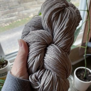 Grey yarn hand dyed with natural dye made from avocado skins and iron.